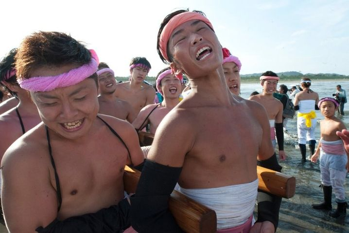 epa04944403 Japanese young people sing traditional festival songs while carrying sacred shrines into the ocean for purification during the Ohara Naked Festival in Ohara town, Chiba Province, 23 September 2015. 18 portable shrines are carried into the ocean during the first day of the two-day event. Japanese fishermens' festivals are often violent in nature, in comparision to farming festivals which are more peaceful. Until the 1960's participants in the Ohara naked festival wore only loincloths. EPA/EVERETT KENNEDY BROWN +++(c) dpa - Bildfunk+++