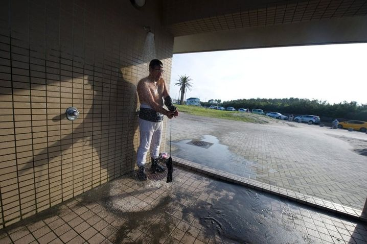 epa04944397 Japanese fishermen washes salt water from his body after the Ohara Naked Festival in Ohara town, Chiba Province, 23 September 2015. 18 portable shrines are carried into the ocean during the first day of the two-day event. Japanese fishermens' festivals are often violent in nature, in comparision to farming festivals which are more peaceful. Until the 1960's participants in the Ohara naked festival wore only loincloths. EPA/EVERETT KENNEDY BROWN +++(c) dpa - Bildfunk+++