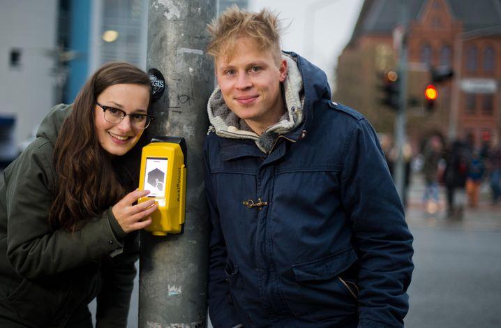 Die Studenten Amelie Künzler und Sandro Engel stehen am 18.11.2014 neben ihrer selbstentwickelten Streetpong-Ampel in Hildesheim (Niedersachsen). Die zwei Studenten der Hochschule für angewandte Wissenschaft und Kunst (HAWK) in Hildesheim haben ein Spiel entwickelt, das Langeweile an der Ampel vertreiben soll. Mit dem Videospiel _Pong_ können Fußgänger die Wartezeiten an einer roten Ampel spielerisch überbrücken. Foto: Julian Stratenschulte/dpa +++(c) dpa - Bildfunk+++