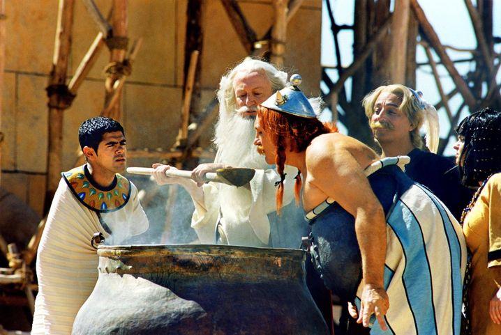 """Verwundert steht der Architekt Numerobis (Jamel Debbouze, l.) im neuen Kinofilm """"Asterix & Obelix - Mission Kleopatra"""" neben einem Kessel, aus dem Miraculix (Claude Rich, M.) Zaubertrank an Obelix (Gerard Depardieu, r.) und Asterix (Christian Clavier, rechts hinten) verteilt. Numerobis soll für die ägyptische Königin Kleopatra in nur drei Monaten einen Palast errichten. Seine instabilen Baukonstruktionen sorgen für Probleme. Schließlich rennt ihm nicht nur die Zeit davon, sein Vorhaben wird außerdem von heimtückischen Konkurrenten sabotiert. Starttermin: 07.03.2002 dpa"""