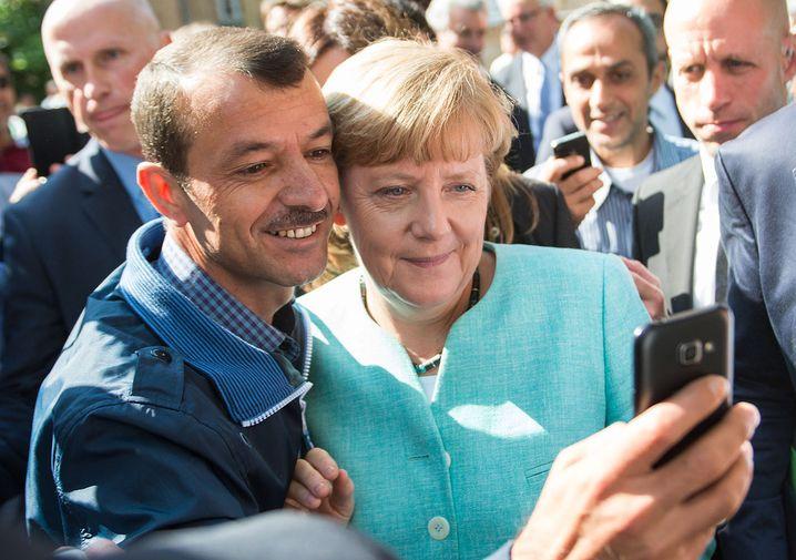 """ARCHIV - Bundeskanzlerin Angela Merkel (CDU) l‰sst sich am 10.09.2015 nach dem Besuch einer Erstaufnahmeeinrichtung f¸r Asylbewerber der Arbeiterwohlfahrt (AWO) und der Auflenstelle des Bundesamtes f¸r Migration und Fl¸chtlinge in Berlin-Spandau f¸r ein Selfie zusammen mit einem Fl¸chtling fotografieren. Foto: Bernd von Jutrczenka/dpa (zu dpa """"Merkel erˆrtert mit CDU-Basis neue Programmatik - Auftakt in NRW"""") +++(c) dpa - Bildfunk+++"""