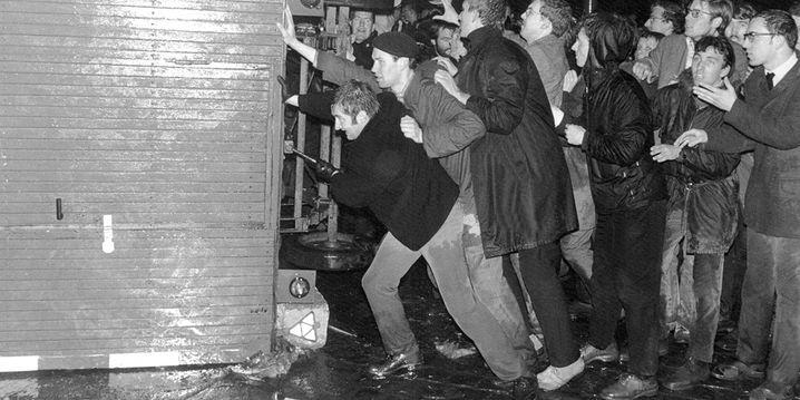 """ARCHIV†- Demonstranten versuchen am Abend des 13.4.1968 vor der Frankfurter Societ‰ts-Druckerei, in der eine Teilauflage der ´Bildª-Zeitung gedruckt wurde, die Ausg‰nge zu verbarrikadieren, um die Auslieferung der Zeitung zu verhindern. Eine Welle von Protestdemonstrationen gegen ´Bildª folgre damals dem Attentat auf den SDS-Ideologen Rudi Dutschke. Die Demonstrationen, die das ganze Osterwochenende 1968 anhielten, richteten sich gegen die Bild und den Axel-Springer-Verlag, der vom SDS als ´Zentrum der systematischen Hetzkampagne gegen politische Minderheitenª bezeichnet wurde. Sechzig Jahre nach Gr¸ndung der ´Bildª-Zeitung kann sich das Boulevardblatt nach den Worten von Chefredakteur Diekmann auf Leser aus der ganzen Gesellschaft st¸tzen. ´Es ist uns gelungen, """"Bild"""" in die Mitte der Gesellschaft zu f¸hrenª, sagte Diekmann der Nachrichtenagentur dpa in Berlin. (Zu dpa ´Zwischen Boulevard und vierter Gewalt - 60 Jahre Bildª). Foto: Roland Witschel **†NUR†SW†** +++(c) dpa - Bildfunk+++"""