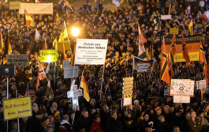 Anhänger der Pegida (Patriotische Europäer gegen die Islamisierung des Abendlandes) demonstrieren am Abend des 26.10.2015 auf dem Theaterplatz mit Plakaten und Deutschland-Fahnen. Zum Gegenprotest aufgerufen hat eine Initiative Gepida - was als Abkürzung für «Genervte Einwohner protestieren gegen Intoleranz Dresdner Außenseiter» steht. Foto: Arno Burgi/dpa +++(c) dpa - Bildfunk+++