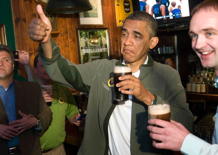 U.S. President Barack Obama (C) gives a thumbs-up as he celebrates St. Patrick's Day with a pint of Guinness during a stop at the Dubliner Irish pub in Washington, March 17, 2012. REUTERS/Jonathan Ernst (UNITED STATES - Tags: POLITICS SOCIETY TPX IMAGES OF THE DAY) - RTR2ZI11