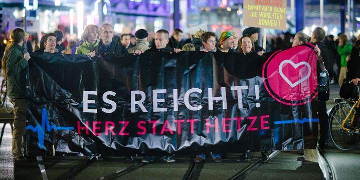 """Demonstranten tragen am Abend des 09.11.2015 in Dresden (Sachsen) ein Transparent mit dem Slogan """"Es reicht! Herz statt Hetze"""" am Dresdner Hauptbahnhof vor einem Demonstrationszug her. Unter dem gleichnamigen Motto formiert sich heute ein breites B¸ndnis von Pegida-Gegnern, die damit ein Zeichen gegen die Rechtsextremen setzen wollen. Foto: Oliver Killig/dpa +++(c) dpa - Bildfunk+++"""