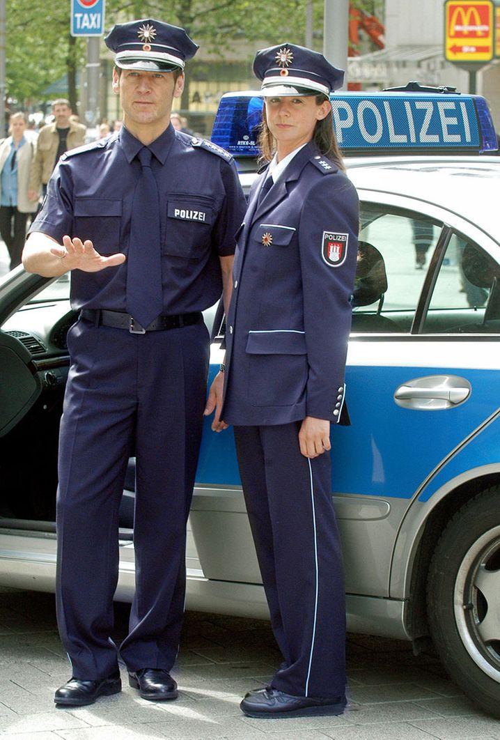 In ihren neuen Uniform stehen Hamburger Polzeibeamte vor ihrem blau-silbernen Dienst-Mercedes bei ihrer ersten Streife in der neuen Dienstbekleidung in der Mˆnckebergstrafle in Hamburg am Dienstag (20.05.2003). Die Uniformen waren am Tag zuvor der ÷ffentlichkeit pr‰sentiert worden. Foto: Frank Rumpenhorst dpa/lno