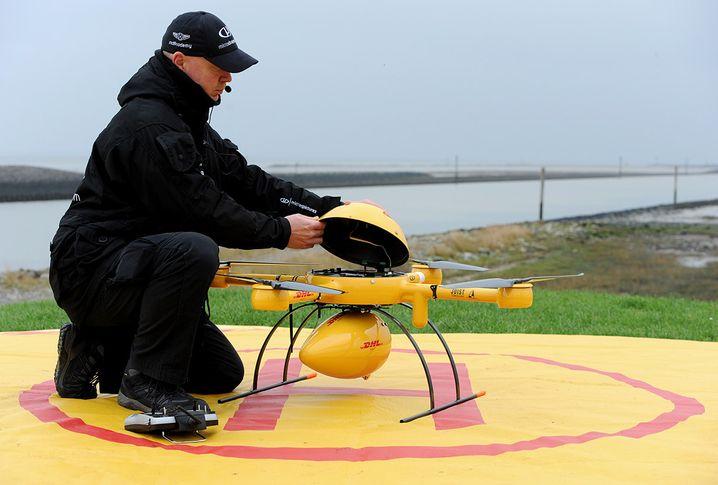 Techniker Elmar Prinz bereitet am 18.11.2014 in Norden-Norddeich (Niedersachsen) den neuartigen DHL Paketkopter auf seinen Start zu der ostfriesischen Insel Juist vor. Nachdem das weltweit einzigartige Projekt f¸r den Transport mit dringend benˆtigten G¸tern mit einer Drohne zu einer Insel erfolgreich funktioniert, wurde es nun offiziell den Medien vorgef¸hrt. Foto: Ingo Wagner/dpa +++(c) dpa - Bildfunk+++