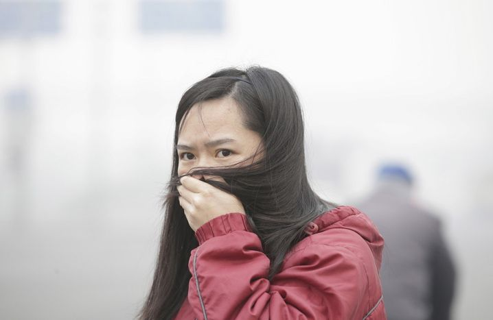 A woman covers her mouth with her hair amid heavy smog in Beijing, China, November 30, 2015. REUTERS/Jason Lee - RTX1WFPO