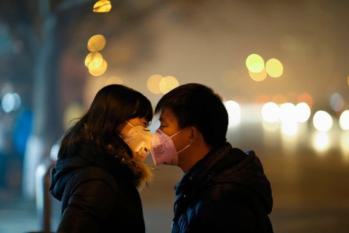 BEIJING, CHINA - NOVEMBER 30: A couple wearing face masks talk at bus station on a polluted evening on November 30, 2015 in Beijing, China. The representatives of the governments of more than 190 countries are meeting in Paris this week, including Chinese President Xi Jinping will attend the Paris meeting. (Photo by Lintao Zhang/Getty Images)