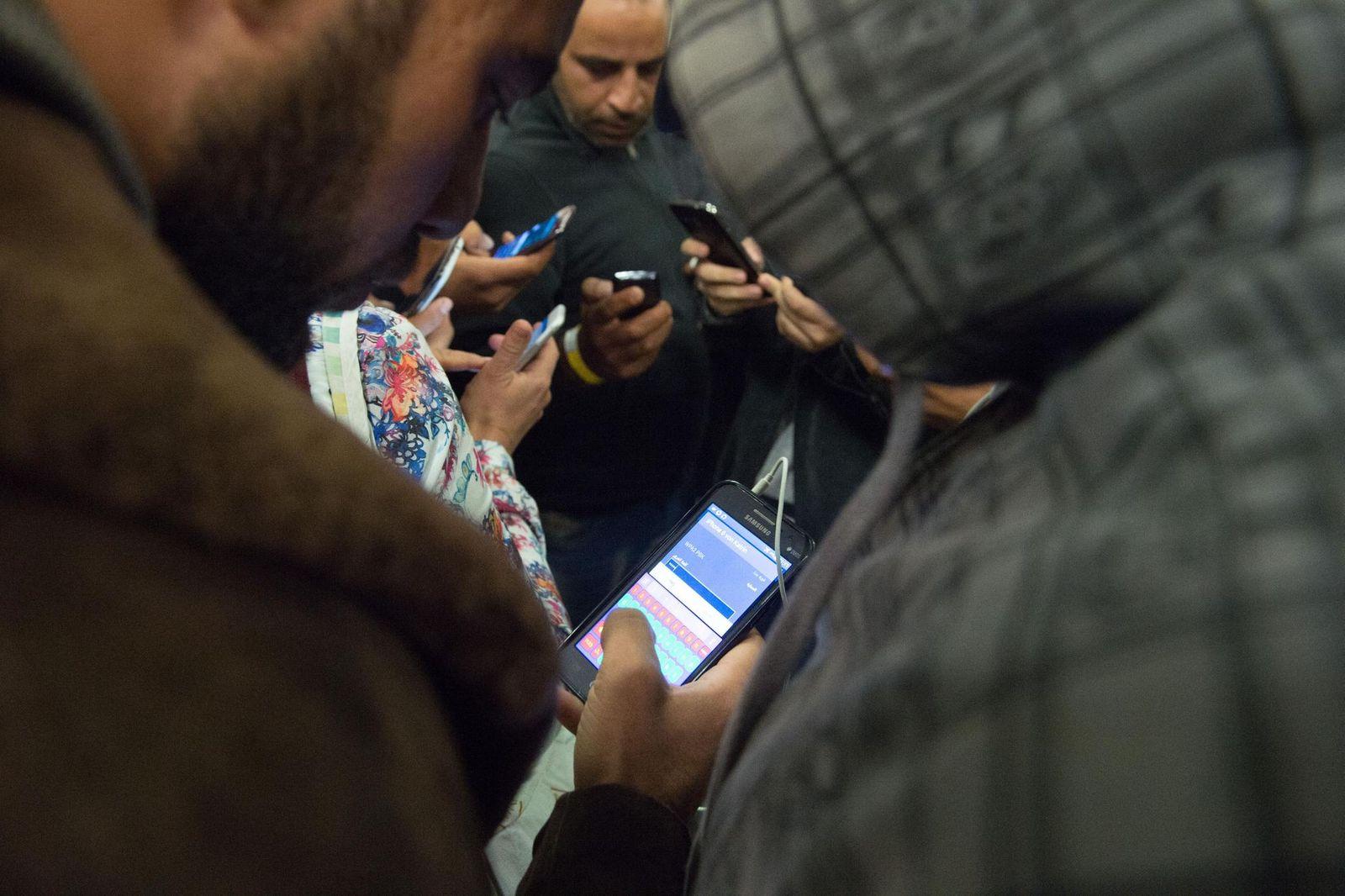 Geflüchtete mit Smartphones