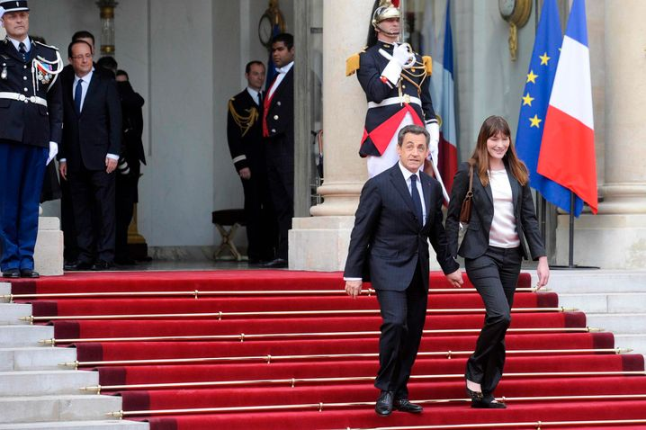 epa03219594 New French President Francois Hollande (2-L, background) looks at outgoing French President Nicolas Sarkozy and former First Lady Carla Bruni Sarkozy (R) leaving after a handover ceremony at the Elysee Palace, in Paris, France, 15 May 2012. Francois Hollande as the 24th President of the French Republic was inaugurated as France's first Socialist president in 17 years 15 May, taking over power from Nicolas Sarkozy in a ceremony at the Elysee Palace. EPA/YOAN VALAT +++(c) dpa - Bildfunk+++