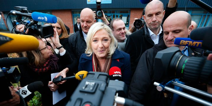 Marine Le Pen, French National Front political party leader and candidate for the National Front in the Nord-Pas-de-Calais-Picardie region, speaks to journalists as she leaves the polling station after casting her ballot in the second-round regional elections in Henin-Beaumont, France, December 13, 2015. REUTERS/Yves Herman - RTX1YGET