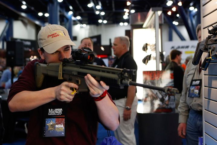 FILE - epa03686670 Ian Futch, 15, looks through the scope of a FNH USA gun during the 2013 National Rifle Association (NRA) Annual Meetings & Exhibits at the George R. Brown Convention Center in Houston, Texas, USA, 03 May 2013. The National Rifle Association is a nonprofit organization that promotes firearm ownership, as well as police training, firearm safety, marksmanship, hunting and self-defense training in the United States. The association has over four million members. EPA/AARON M. SPRECHER (zu dpa-Reportage «Kinderspiel»: Warum Amerikaner von Waffen besessen sind» vom 29.10.2015) +++(c) dpa - Bildfunk+++