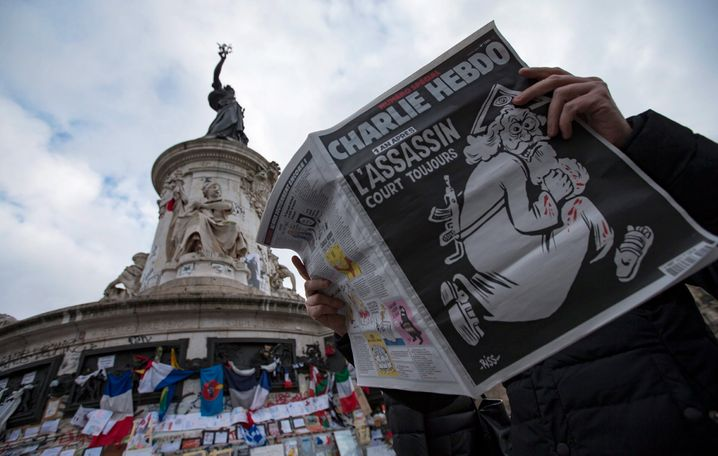 epa05089591 A man reads a copy of French satirical newspaper Charlie Hebdo's one-year anniversary edition of last year's January attacks near the makeshift memorial site on Place de la Republique in Paris, France, 06 January 2016. France this week commemorates the victims of last year's Islamist militant attacks on satirical weekly Charlie Hebdo and a Jewish supermarket with eulogies, memorial plaques and another cartoon lampooning religion. The cover of the special issue No. 1224 of the French satirical weekly Charlie Hebdo with a cartoon of a bearded god carrying a kalashnikov reading '1 an apres. L'assassin court toujours' (lit: One year later.The murderer is still on the run). EPA/IAN LANGSDON +++(c) dpa - Bildfunk+++