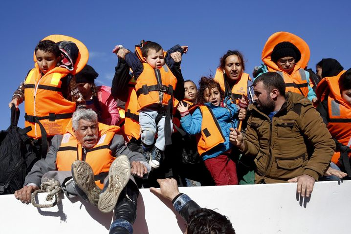Refugees and migrants try to leave a boat as they arrive on the Greek island of Lesbos, November 26, 2015. REUTERS/Giorgos Moutafis TPX IMAGES OF THE DAY - RTX1VZJL