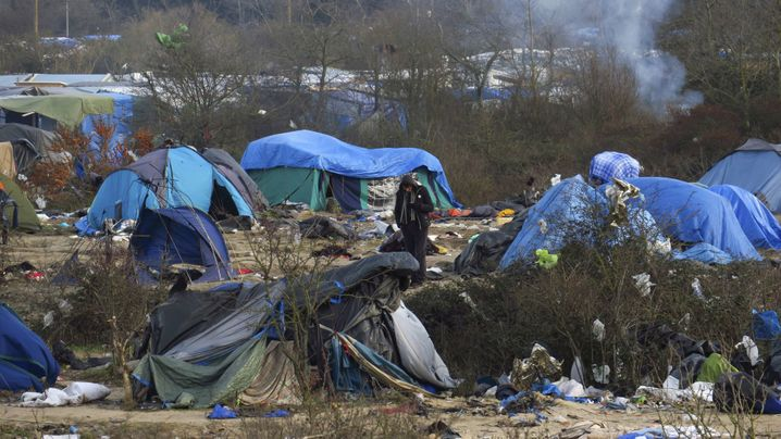 """A migrant stands among dismantled shelters of the camp known as the """"Jungle"""", a squalid sprawling camp in Calais, northern France, January 18, 2016. French authorities have asked migrants living in makeshift shelters to respect an unoccupied 100 meter zone from the fence barrier which protects the road that leads to the ferry terminal . REUTERS/Pascal Rossignol - RTX22XGC"""