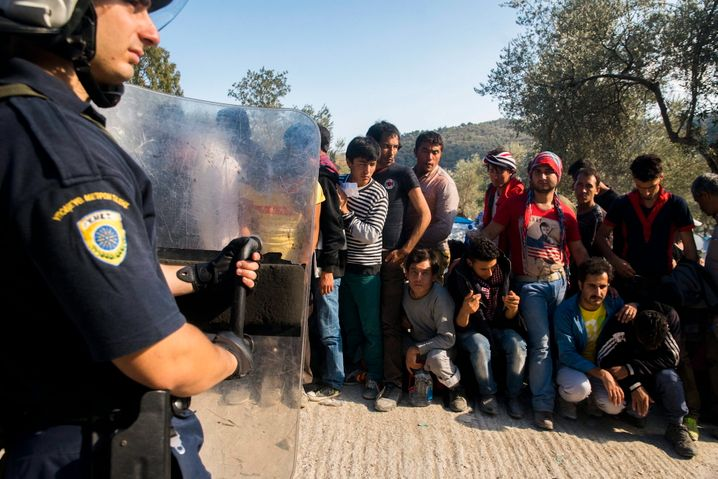 epa04966540 Migrants are guarded by a Greek policeman as they wait to be registered in a camp set up for migrants from Afghanistan near Moria on the island of Lesbos, Greece, 06 October 2015. EPA/Zoltan Balogh HUNGARY OUT +++(c) dpa - Bildfunk+++