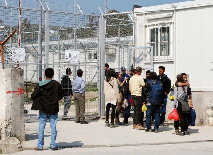 Fl¸chtlinge und Fl¸chtlingshelfer stehen am 21.03.2016 am Tor des Auffanglagers ´Moriaª†auf der griechischen Insel Lesbos in der Hafenstadt Mitilini (Mytilini). Am Montagmittag schlossen sich ¸berraschend die Tore des Auffanglagers ´Moriaª auf Lesbos. In dieser ehemaligen Haftanstalt der Insel sollen k¸nftig offensichtlich nur noch jene Migranten untergebracht werden, die seit dem Inkrafttreten des EU-Fl¸chtlingspakts am Sonntag angekommen sind. Foto: Alexia Angelopoulou/dpa (zu dpa ´Lesbos r‰umt auf: Die chaotische Realit‰t des Fl¸chtlingspaktsª vom 21.03.2016) +++(c) dpa - Bildfunk+++