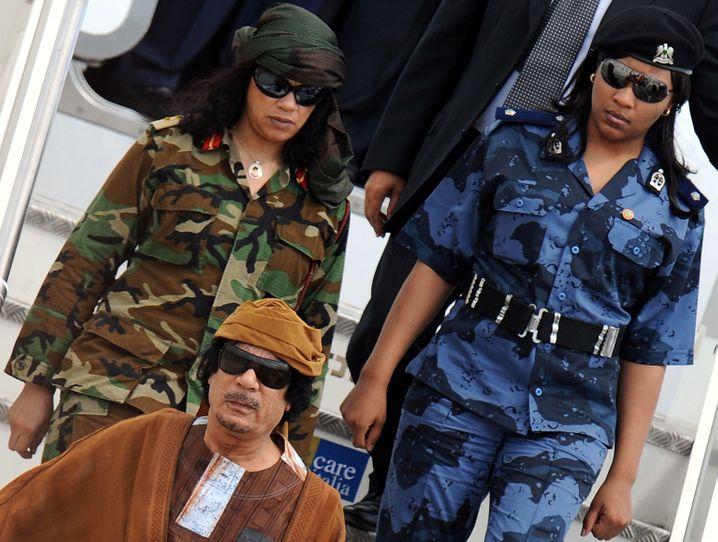 FILE - Libyens Staatschef Muammar al-Gaddafi kommt mit zwei seiner Leibwächterrinnen in Rom, Italien, am Flughafen an, am 29.08.2010. Die Führung der libyschen Rebellen hat keine Kenntnis vom Versteck des bisherigen Machthabers Muammar al-Gaddafi. «Niemand weiß, wo Gaddafi ist», sagte der Vorsitzende des nationalen Übergangsrates am Montag (22.08.2011) dem arabischen TV-Sender Al Arabija. EPA/ETTORE FERRARI +++(c) dpa - Bildfunk+++  