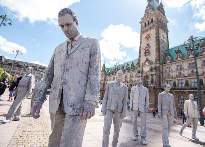 Aktivisten in Lehmkleidung ziehen am 17.06.2017 in Hamburg während der Kunstprotestaktion «1000 Gestalten» über den Rathausmarkt. Um ein Zeichen für mehr Solidarität und politische Partizipation zu senden sind drei Wochen vor dem G20-Gipfel die ersten von «1000 Gestalten» durch die Hamburger Innenstadt gezogen. Foto: Daniel Bockwoldt/dpa +++(c) dpa - Bildfunk+++ | Verwendung weltweit