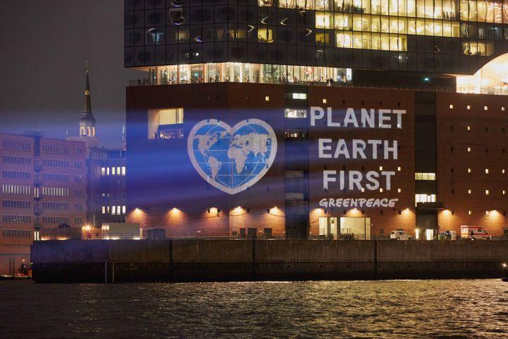 Aktivisten von Greenpeace projizieren am 15.06.2017 eine herzförmige Erde mit der Forderung «Planet Earth First» auf die Elbphilharmonie in Hamburg. Foto: Georg Wendt/dpa +++(c) dpa - Bildfunk+++ | Verwendung weltweit