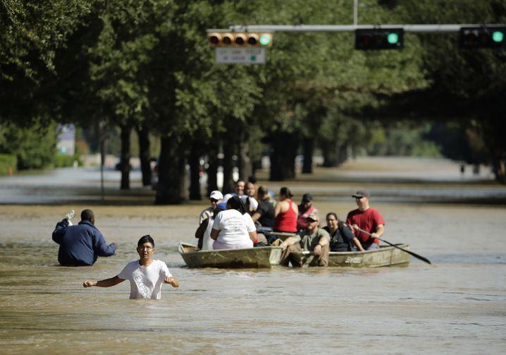 Anwohner sitzen am 30.08.2017 in Houston (USA) in einem Boot während ihrer Evakuierung.Sie mussten ihre in dem Addicks Reservoir und Damm nahegelegenen Häuser verlassen. Der Tropensturm Harvey hatte weite Teile Texas und Louisianas überflutet. Foto: Charlie Riedel/AP/dpa +++(c) dpa - Bildfunk+++  