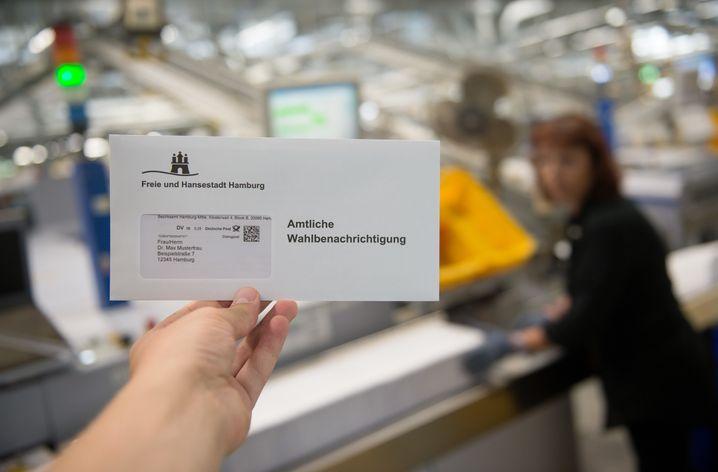 Ein Musterbrief für eine Wahlbenachrichtigung für die Bundestagswahl wird am 18.08.2017 im Briefzentrum Altona in Hamburg vor eine Sortiermaschine gehalten. Am 24. September wird ein neuer Bundestag gewählt. Foto: Daniel Reinhardt/dpa +++(c) dpa - Bildfunk+++ | Verwendung weltweit