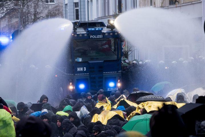 Die Polizeibeamten räumen mit Wasserwerfern am 02.12.2017 eine von Demonstranten besetze Straße nahe des HCC Hannover Congress Centrum in Hannover (Niedersachsen). Der Bundesparteitag der Alternative für Deutschland findet in Hannover statt. Foto: Peter Steffen/dpa +++(c) dpa - Bildfunk+++ | Verwendung weltweit