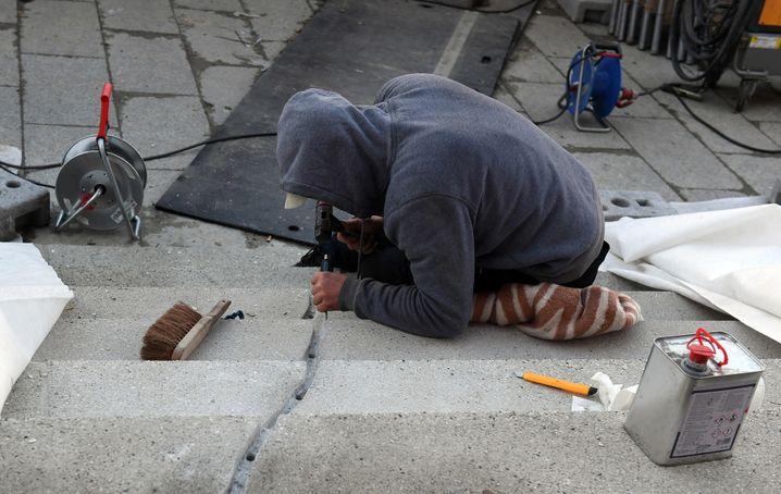 Eine Fachkraft arbeitet am 18.12.2017 in Berlin am Anschlagsort auf dem Weihnachtsmarkt am Breitscheidplatz am Denkmal für die bei dem Terroranschlag getöteten Menschen. Bei dem Anschlag mit einem Lastwagen tötete ein islamistischer Terrorist am 19. Dezember vergangenen Jahres 12 Menschen und verletzte etwa 70. Foto: Maurizio Gambarini/dpa +++(c) dpa - Bildfunk+++ | Verwendung weltweit