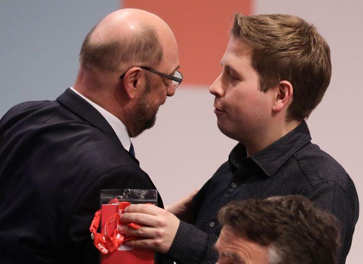 Bundesparteitag der SPD am 07.12.2017 in Berlin. Der Juso-Vorsitzende Kevin Kühnert (r) umarmt den Parteivorsitzenden Martin Schulz nach den Abstimmungen über verschiedene Anträge zu Sondierungsgesprächen für eine große Koalition. Foto: Kay Nietfeld/dpa +++(c) dpa - Bildfunk+++   Verwendung weltweit