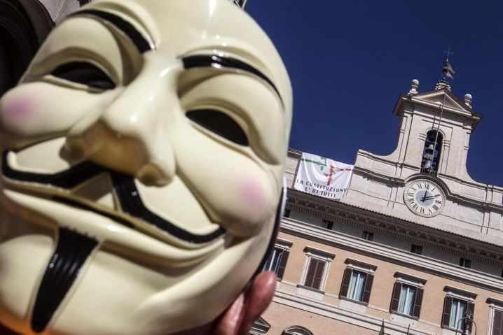 epa03855778 An unidentified supporter of oppositional Five Star Movement party (MoVimento 5 Stelle, M5S) wears an Anonymous masn as he stands in front of the Italian Parliament at Montecitorio square in Rome, Italy, 07 September 2013. M5S MPs occupied the Parliament's roof and slept there to protest against changes to the Italian Constitution. EPA/ANGELO CARCONI +++(c) dpa - Bildfunk+++  