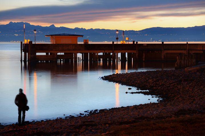Ein Mann steht am 27.12.2013 in Langenargen (Baden-Württemberg) kurz nach Sonnenuntergang am Ufer des Bodensees, während im Hintergrund die Schiffsanlegestelle und die Alpen zu sehen sind. Foto: Felix Kästle/dpa +++(c) dpa - Bildfunk+++ | Verwendung weltweit