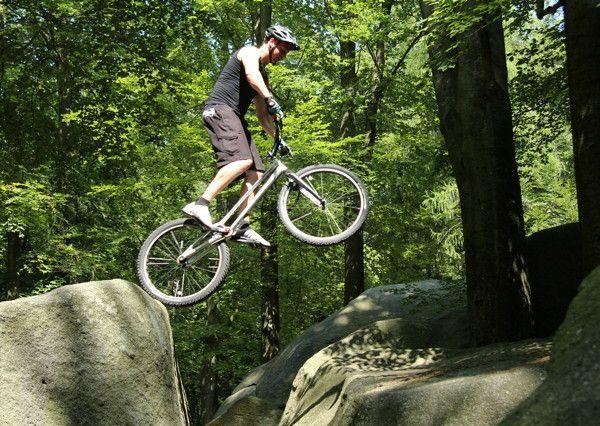 Gewagte Sprünge in voller Körperspannung: Ein Mountainbiker übt am 27.07.2014 im Felsenmeer im hessischen Odenwald. Im Schatten des Waldes oberhalb von Lautertal-Reichenbach (Hessen) ist die Hitze des Sommers leichter zu ertragen _ und die dunkelgrauen Quarzdiorit-Felsen bieten dem Sportler einen herausfordernden Parcours. Das Gelände im Naturschutzgebiet _Felsberg bei Reichenbach_ ist ein beliebtes Naherholungsgebiet für Familien. Foto: Sophie Rohrmeier/dpa +++(c) dpa - Bildfunk+++ | Verwendung weltweit
