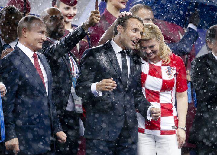 15.07.2018, Russland, Moskau: Fußball: WM, Frankreich - Kroatien, Finalrunde Finale im Luschnikistadion. Emmanuel Macron (M), Präsident von Frankreich, Kolinda Grabar-Kitarovic (r), Staatspräsidentin von Kroatien und Wladimir Putin (l), Präsident von Russland stehen bei der Siegerehrung im Regen. Foto: Petr David Josek/AP/dpa +++ dpa-Bildfunk +++ |