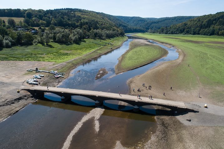 16.08.2018, Hessen, Vöhl: Spaziergänger gehen über die alte Aseler Brücke im Edersee (Luftaufnahme mit einer Drohne). Bauwerke des versunkenen Edersee-Atlantis tauchen derzeit wieder auf. Der Stausee hat zurzeit rund ein Viertel seines Wasserstandes. Foto: Swen Pförtner/dpa +++ dpa-Bildfunk +++ | Verwendung weltweit