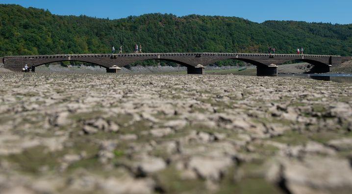 16.08.2018, Hessen, Vöhl: Spaziergänger gehen über die alte Aseler Brücke im Edersee. Bauwerke des versunkenen Edersee-Atlantis tauchen derzeit wieder auf. Der Stausee hat zurzeit rund ein Viertel seines Wasserstandes. Foto: Swen Pförtner/dpa +++ dpa-Bildfunk +++ | Verwendung weltweit