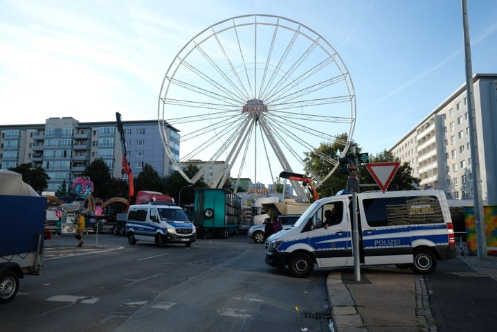 26.08.2018, Sachsen, Chemnitz: Ein Polizeifahrzeuge stehen in der Chemnitzer Innenstadt vor der Kulisse des Stadtfestes. Nach dem verhängnisvollen Streit in der Chemnitzer Innenstadt in der Nacht zu Sonntag mit einem Todesopfer und zwei Verletzten endet das Stadtfest vorzeitig. Danach zogen Hunderte Menschen durch die Innenstadt. Foto: Sebastian Willnow/dpa-Zentralbild/dpa +++ dpa-Bildfunk +++ | Verwendung weltweit