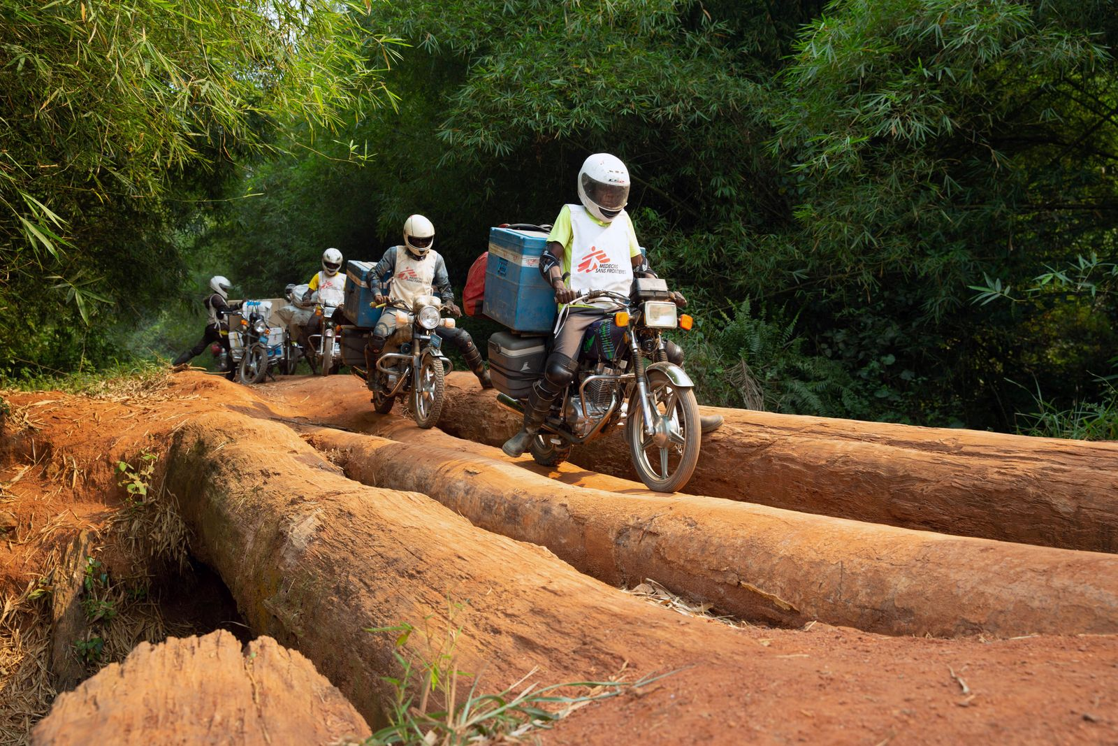 A motorcycle convoy carrying vials of measles vaccine and other supplies for medial NGO Doctors Without Borders crosses a log bridge on a road between Lisala and Boso-Manzi in Mongala province