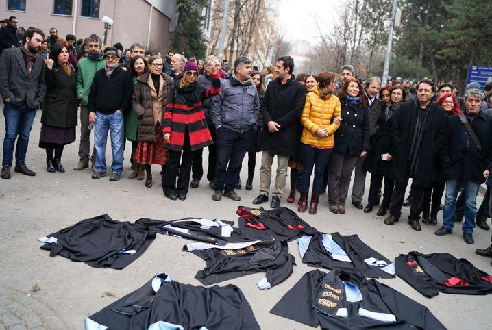 Studenten und Hochschulangehörige legen an der Universität Ankara demonstrativ ihre Umhänge auf den Boden - als Zeichen des Protests.