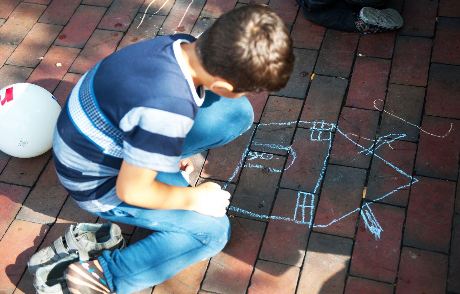 Kinder malen mit Kreide auf die Straße