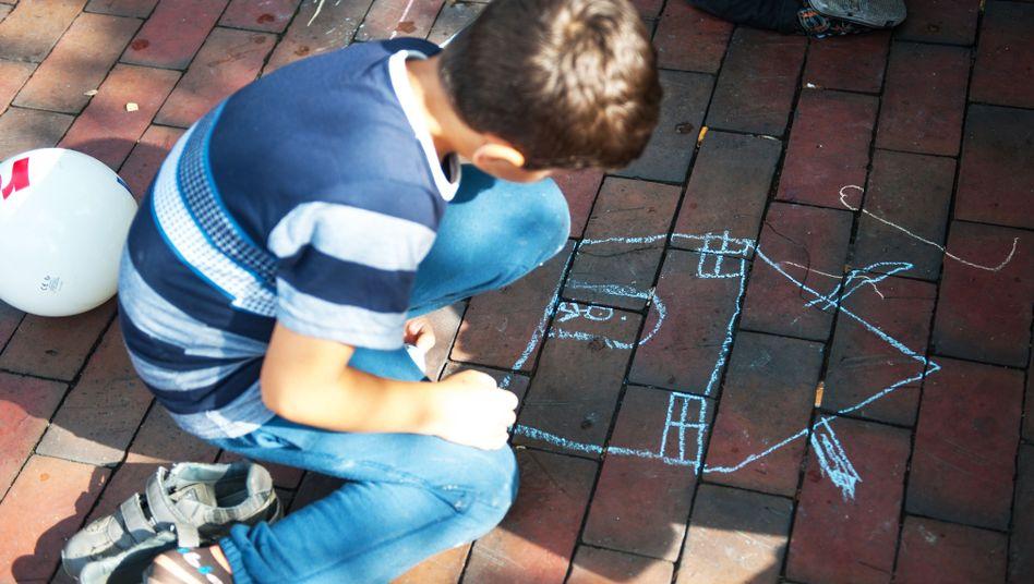 Kind malt ein Kreidebild (Symbolbild)