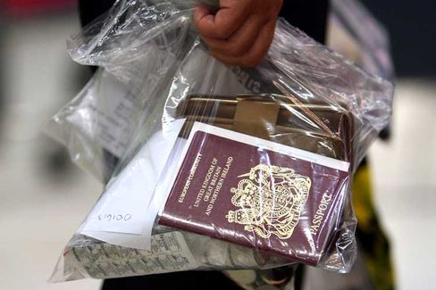 A passenger holds her passport and other items in a plastic bag at Manchester airport.
