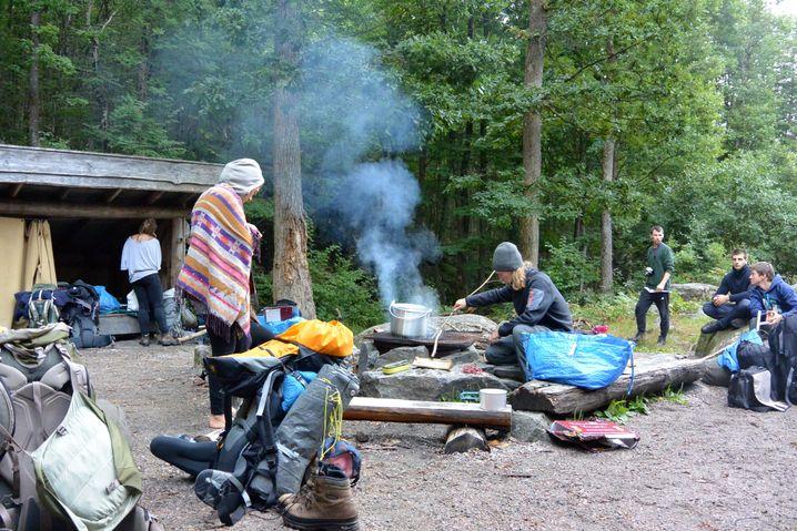 Im Freiluftpark: offene Holzhütten und Feuerstelle am Wald