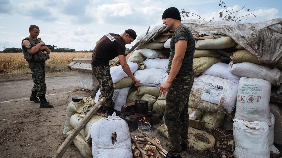 Ukrainische Soldaten mit Mauer aus Sandsäcken bei Slavianoserbsk: Bau zweier riesiger Verteidigungslinien und einer Mauer geplant