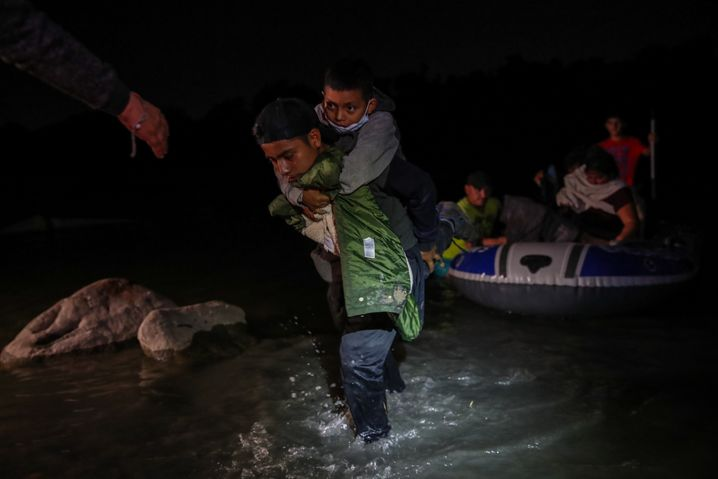 Migrants from Central America wade across the Rio Grande to enter the U.S. from Mexico.