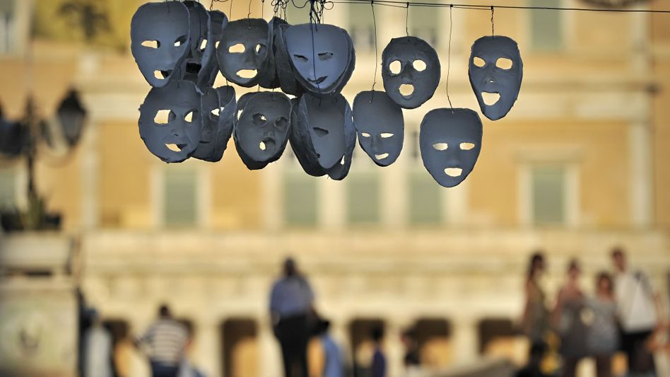 Masks hung by protesters outside the Greek parliament this week. Prime Minister Giorgios Papandreou is urging the European Union to act quickly.
