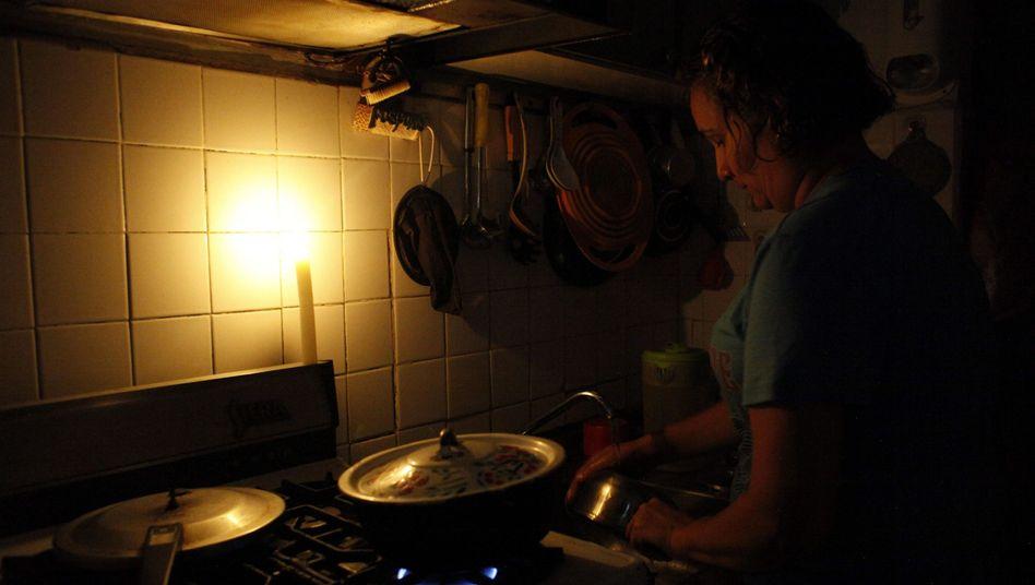 Venezolanerin kocht bei Kerzenlicht.