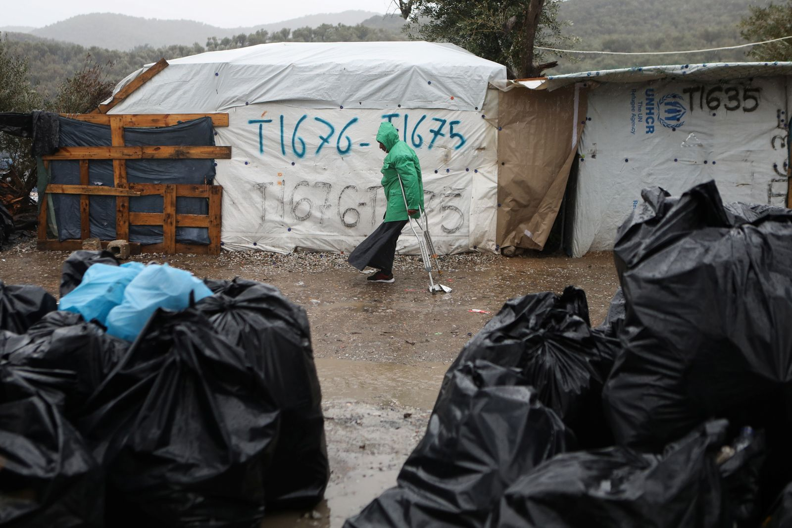 A migrant makes his way during heavy rainfall at a temporary camp for refugees and migrants next to the Moria camp on the island of Lesbos