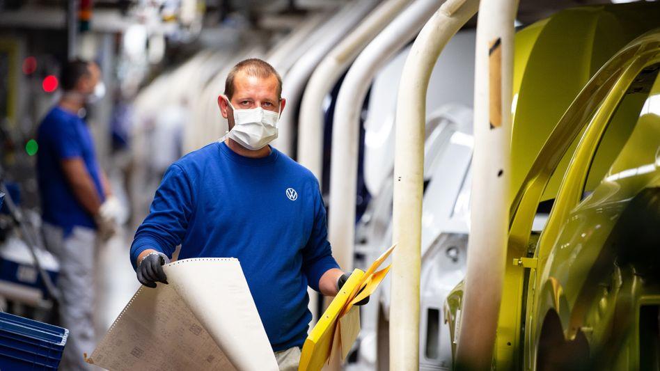 Ein Produktionsmitarbeiter mit Mundschutz bei VW. Die Autoindustrie steckt aufgrund der Coronakrise im größten Wandel seit Jahrzehnten