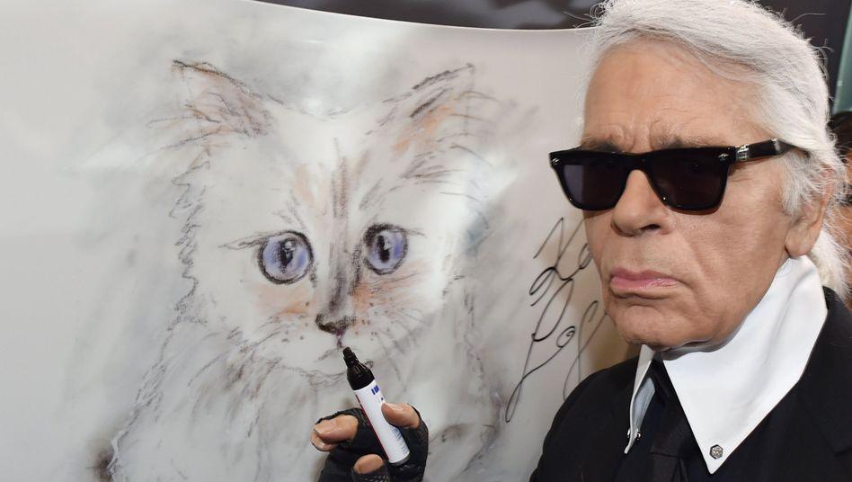 Karl Lagerfeld vor einer Zeichnung seiner Katze Choupette